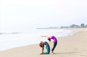 Two women practicing yoga on the beach