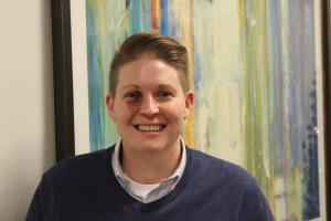 Photo of Amanda Palace, executive director of Astral at Auburn, with painting in the background.