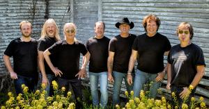 Members of The Outlaws stand against a wall, with all seven wearing black t-shirts.