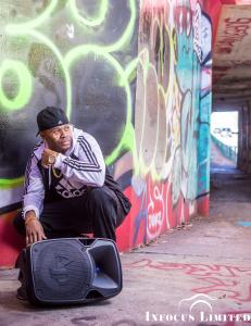 Artist Frequent-C is dressed in a black white Adidas track suit and matching sneakers while squatting near a large speaker in front of brightly-colored graffiti street art in Atlanta.