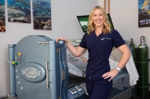 Nicole Garrett next to a Hyperbarics Chamber
