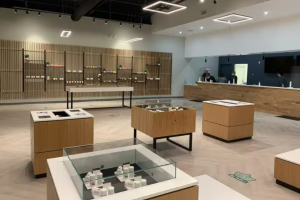 Image of a beautifully built interior for a cannabis dispensary, with high cement ceilings and wooden sound fixtures on the cement walls.
