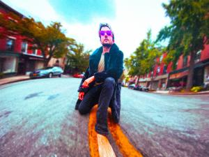 Music composer Frank Cogliano kneeling in the middle of Atlantic Avenue in Brooklyn