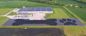 Artist rendering showing PetDine's expansive Harvard IL production facility, parking lot, neighboring fields and rows of solar panels with shaded shapes of a dog bone and pawprint on the panels.