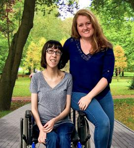 Founder of LoveAbility, Jerrica Mah, posing with her lifelong friend who is in a wheelchair
