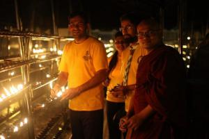 Volunteer Ministers join Buddhist monks in Sri Lanka in lighting candles for peace.